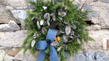 A large premium greens mix comprised of mountain hemlock, American boxwood tips, seeded eucalyptus with 5 white redpine cones, 5 white painted teasels, 2 mini yellow faux pears, finished with a premium blue bow. Cost $123.00